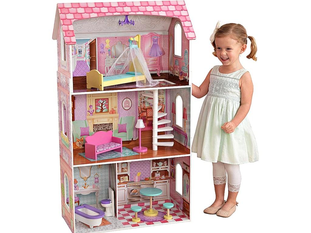 little girl standing next to KidKraft Penelope Dollhouse
