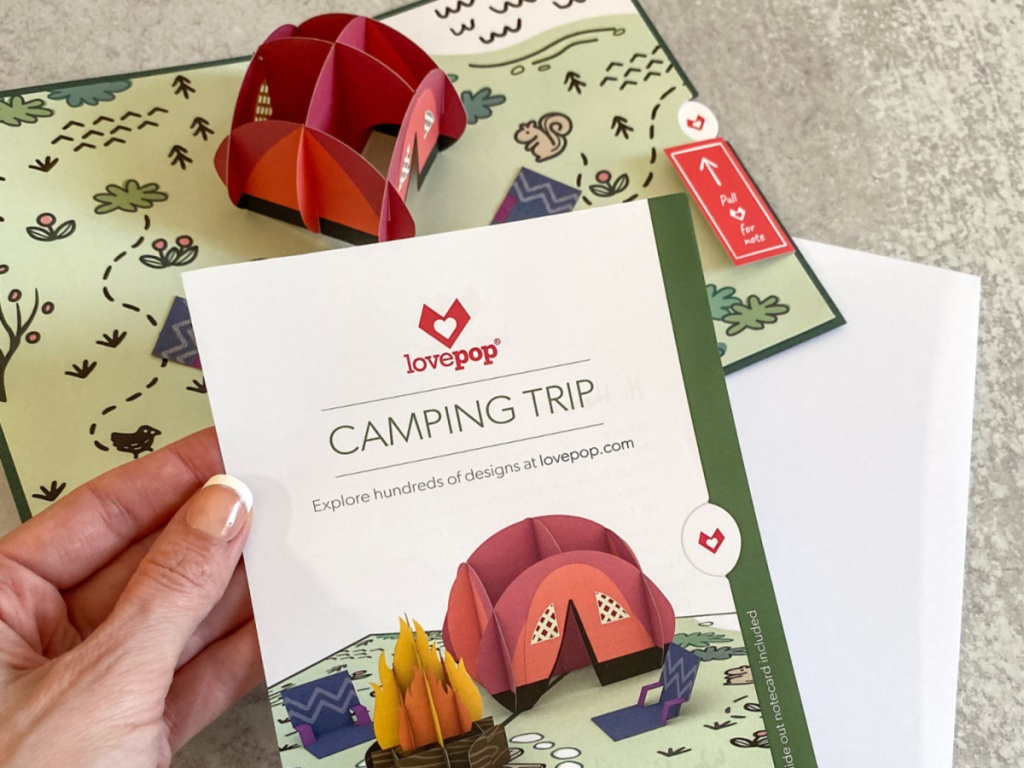 hand holding camping trip card and popup