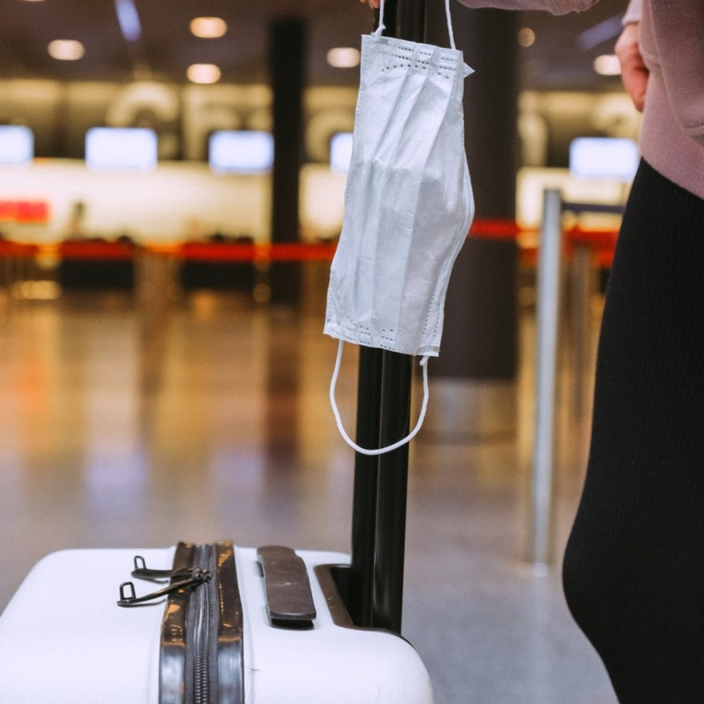 mask hanging on luggage at airport