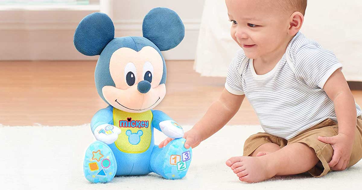 baby playing with mickey mouse plush toy
