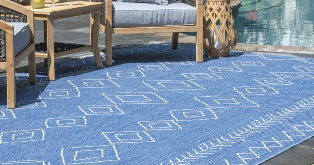 blue diamond rug on patio with pool in background