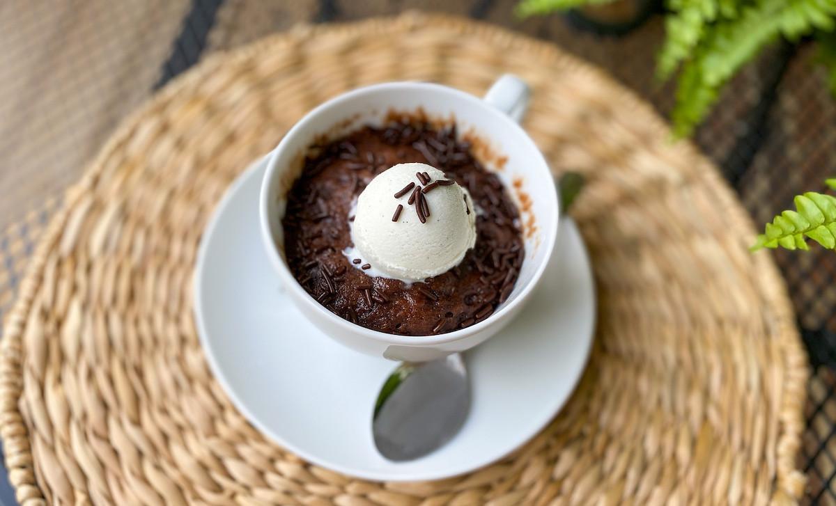white coffee mug with chocolate mug cake and ice cream inside