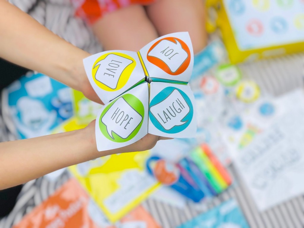 hands holding folded paper toy with words and colors on outside