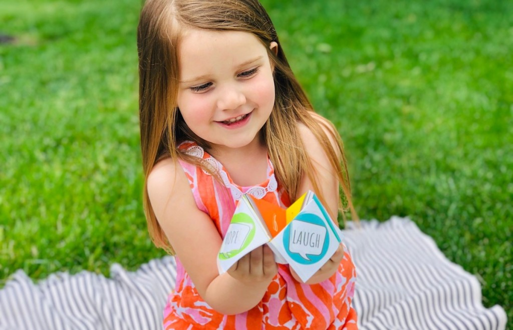 girl holding colorful paper toy in hands smiling