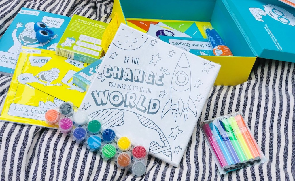 colorful crafts and activities laying on stripe blanket