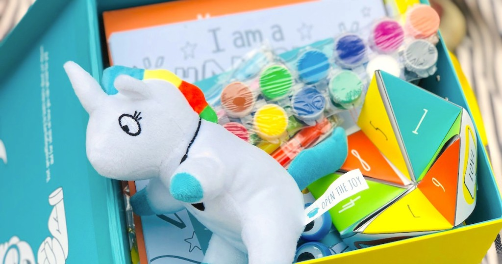 box full of colorful paint stuffed animals and activities