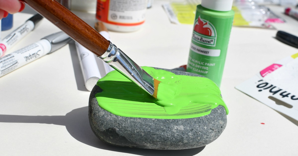 paintbrush painting a rock with green paint