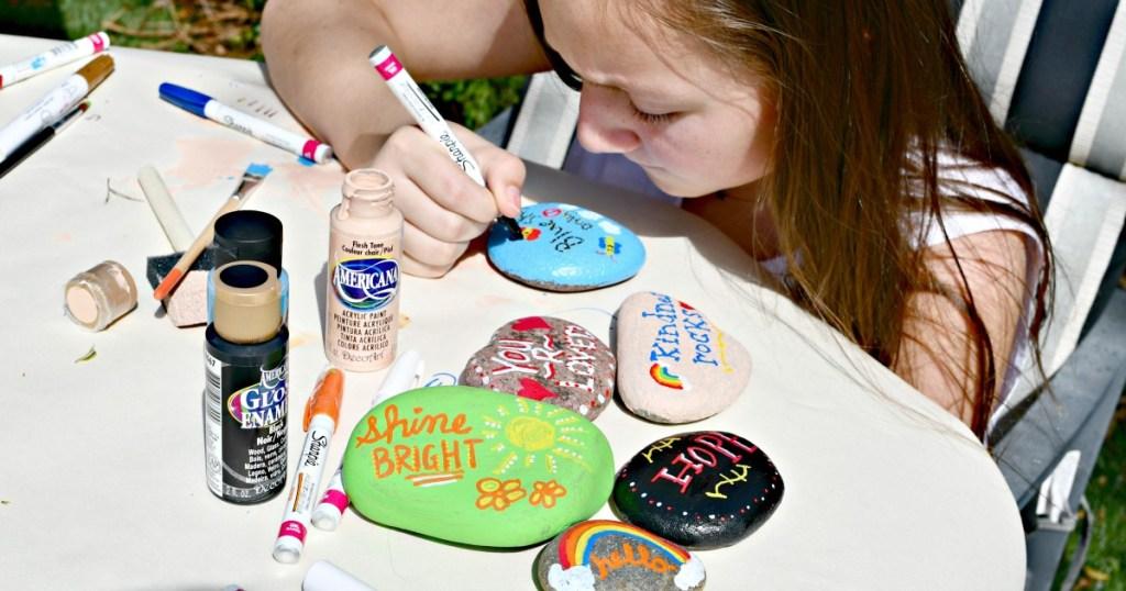 girl painting kindness rocks