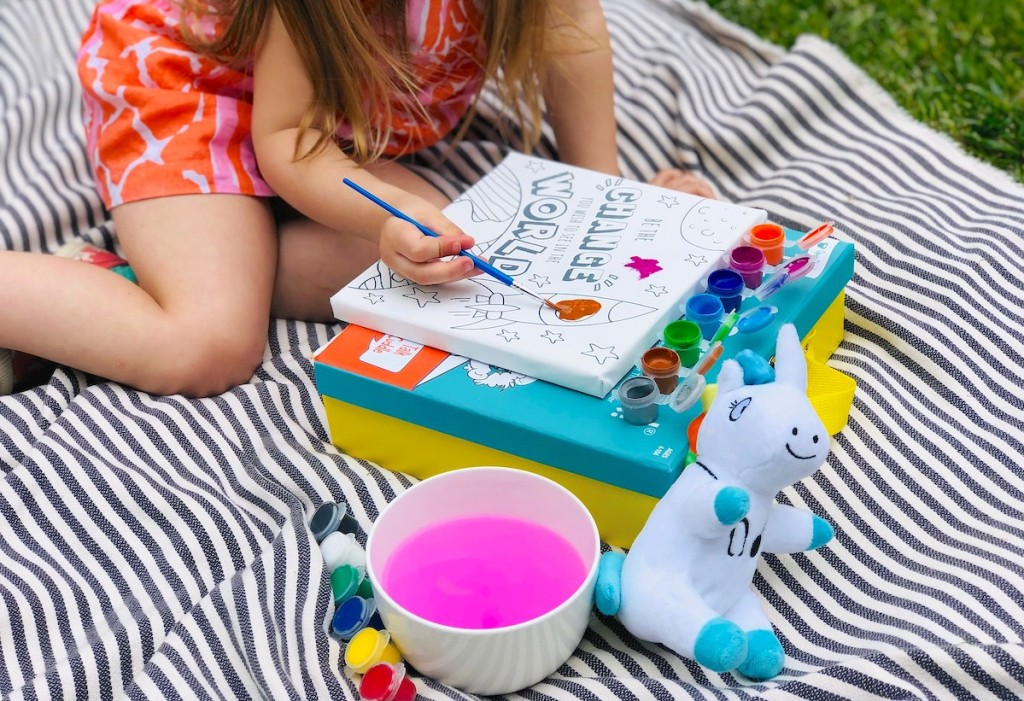 girl painting on blank canvas outside on blanket in grass