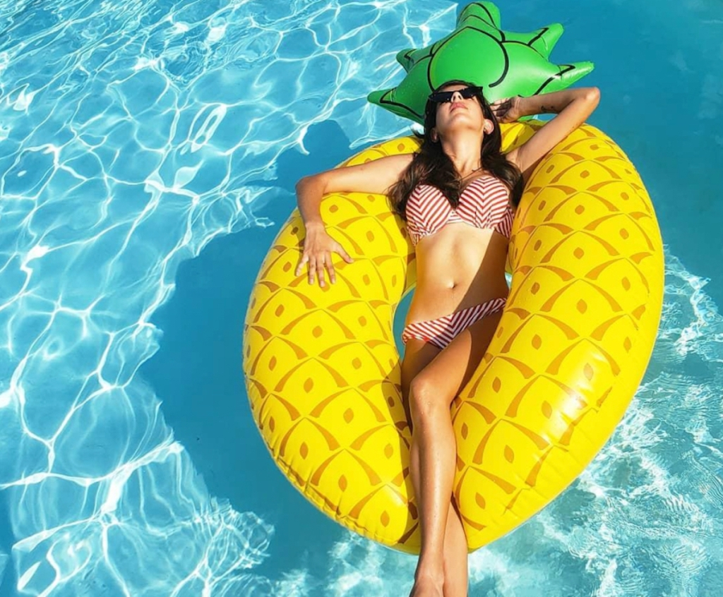 woman floating in water on pineapple pool float