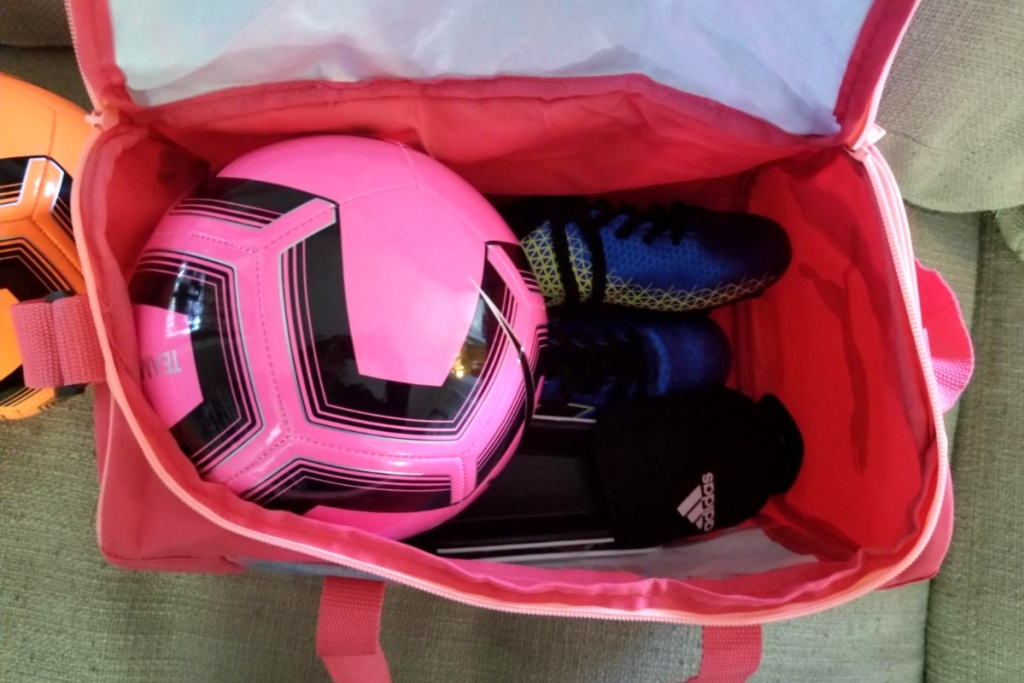 puma duffel opened with soccer ball and cleats in side