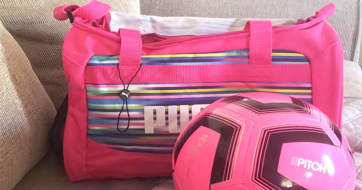 pink Puma duffel bag on a couch with a pink soccer ball