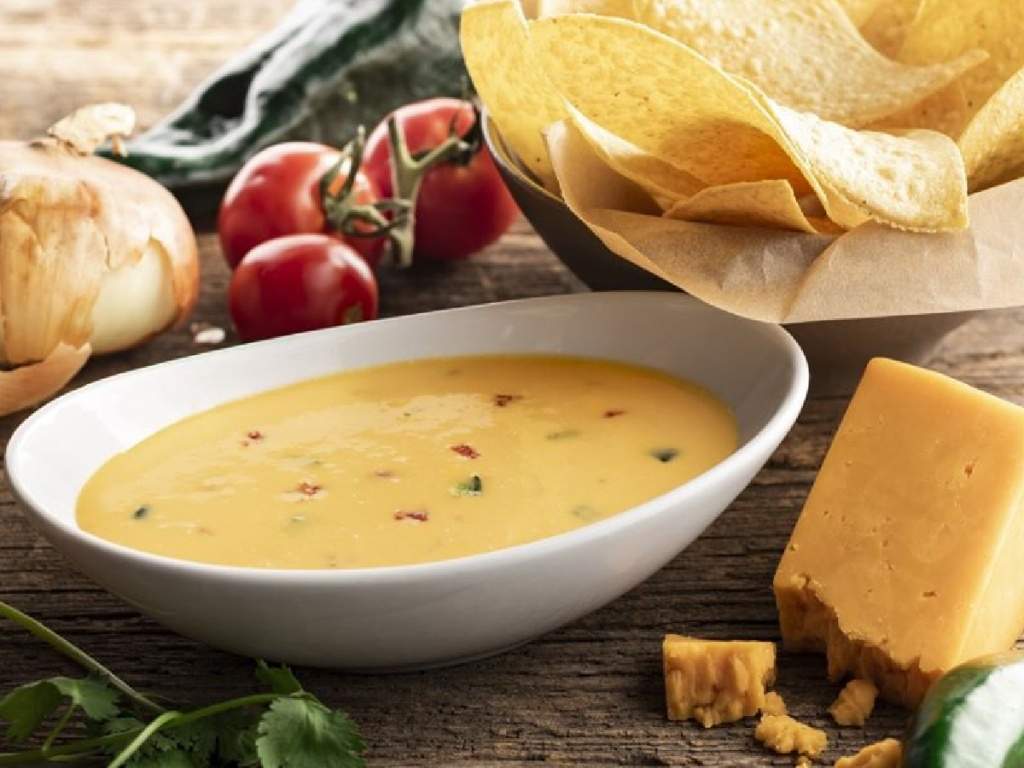 bowl of queso dip with chips, onions, cheese and tomatoes