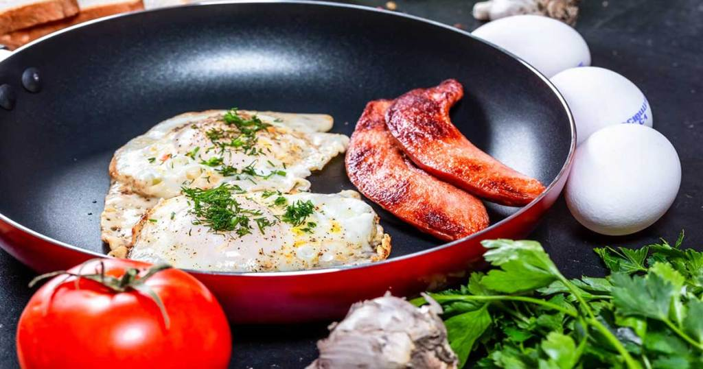 close up of a red skillet with bacon and eggs in it
