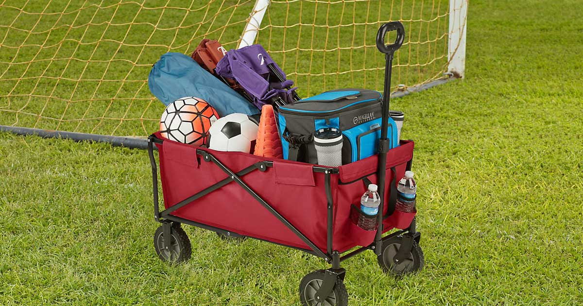 red folding wagon with sports equipment in it on a soccer field
