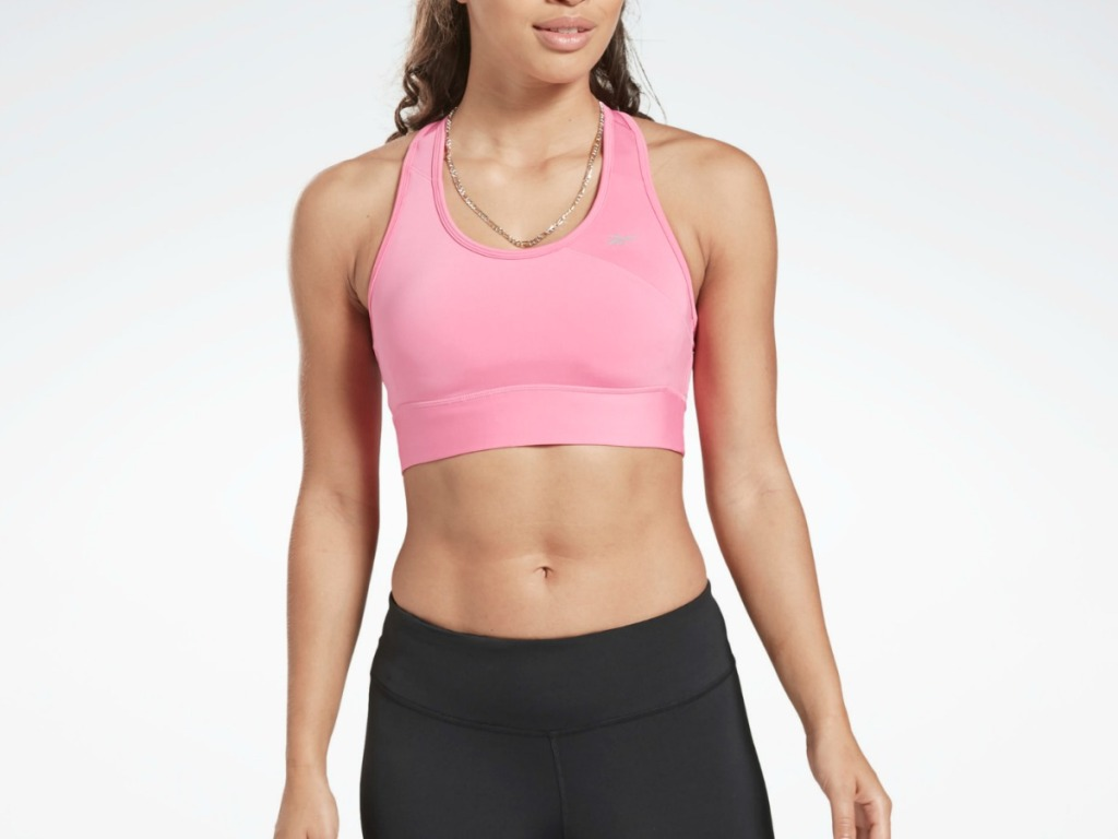 woman wearing pink sports bra and black tights