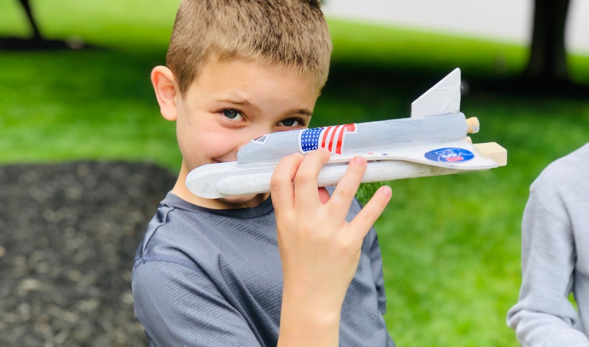 boy holding a wood painted rocket ship