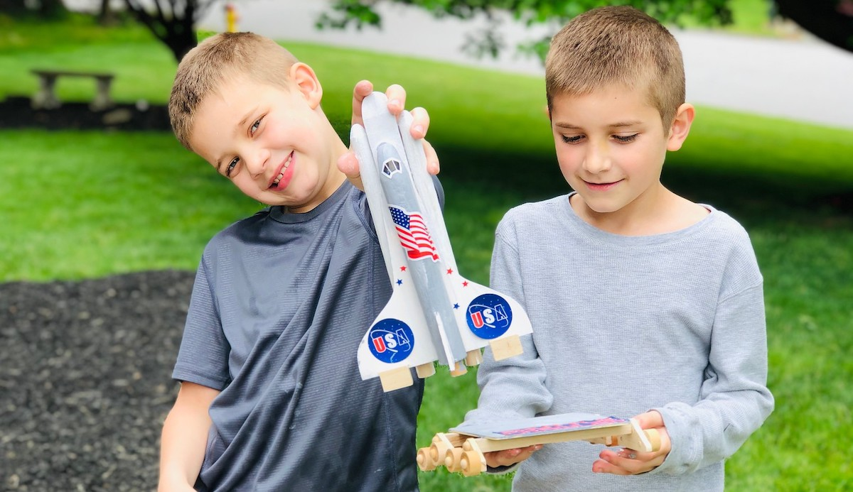 two boys holding wood rocket ship pieces smiling