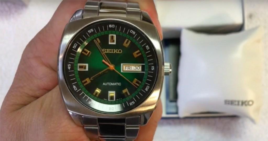 seiko green analog watch in hand