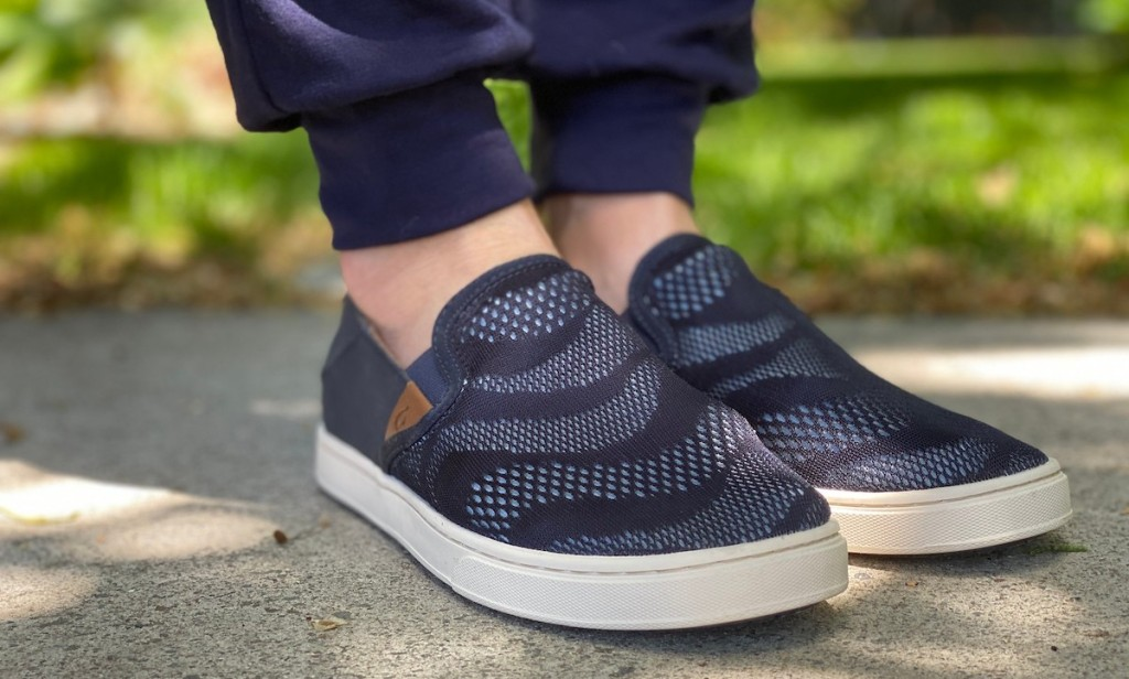 feet wearing blue loafer slip on shoes on concrete outside