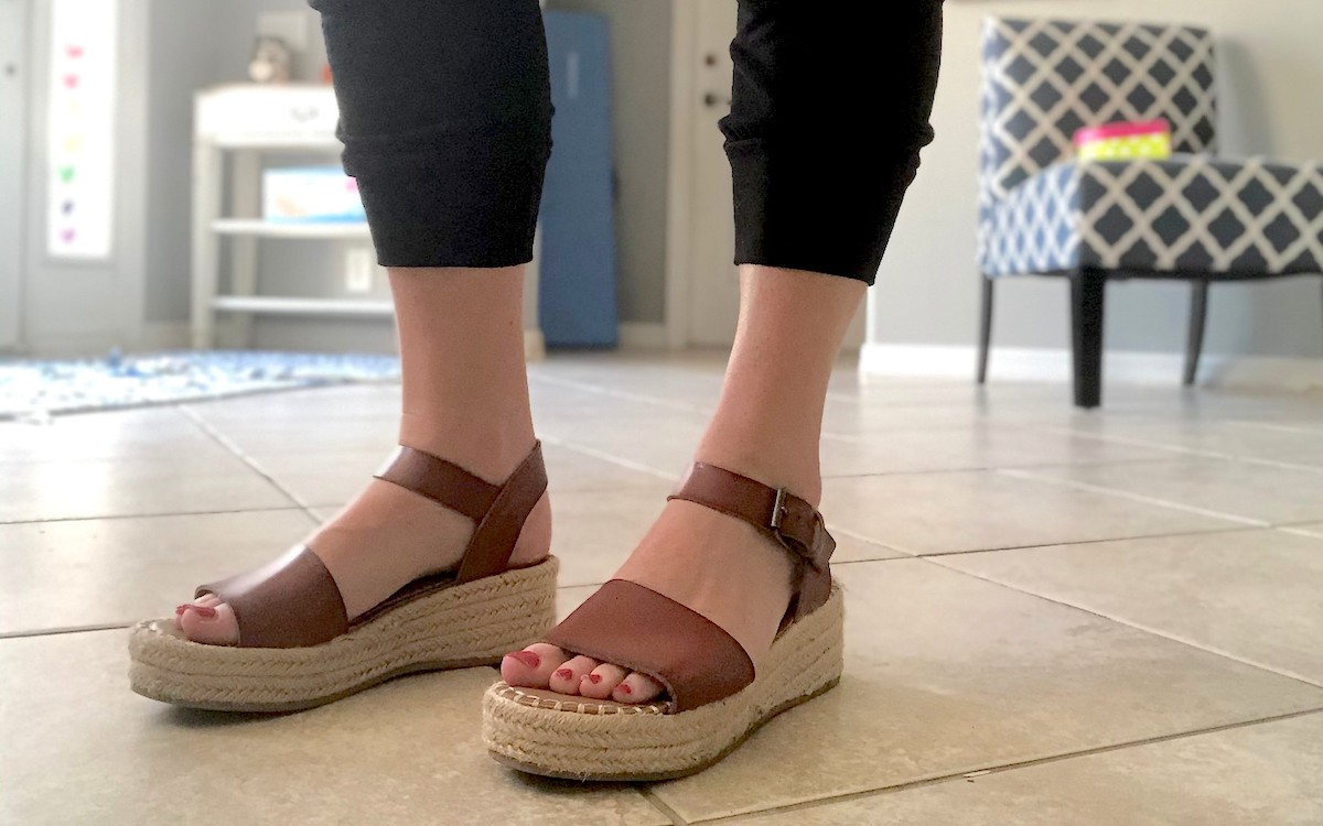 close up of feet wearing brown leather wedge sandals on tile floor