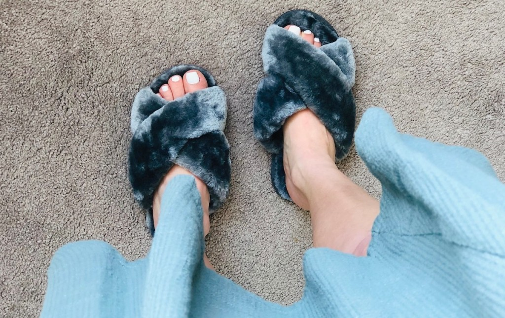feet wearing dark gray fuzzy slippers with sage green dress at knees