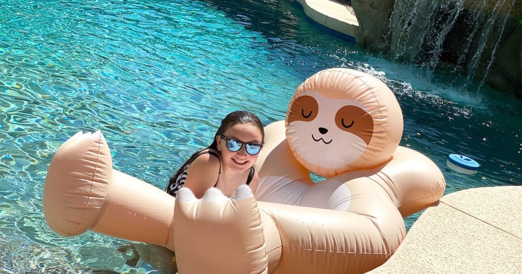 girl wearing sunglasses hanging on sloth pool float in water