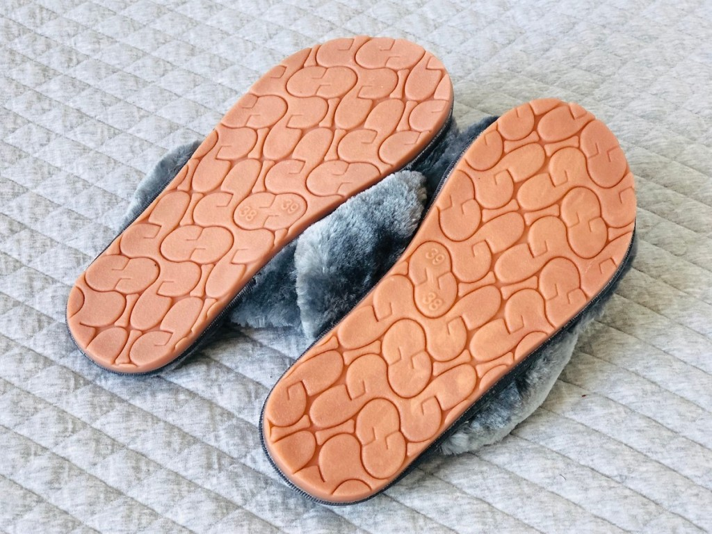 bottoms of slippers laying on quilted light gray blanket