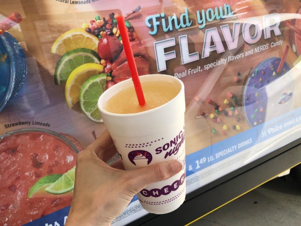 hand holding slush in front of slush ad