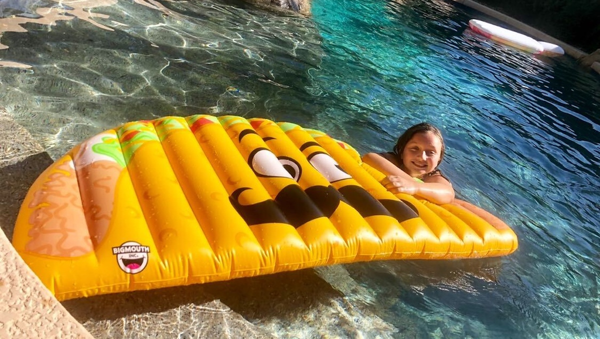 girl resting on taco pool float in water