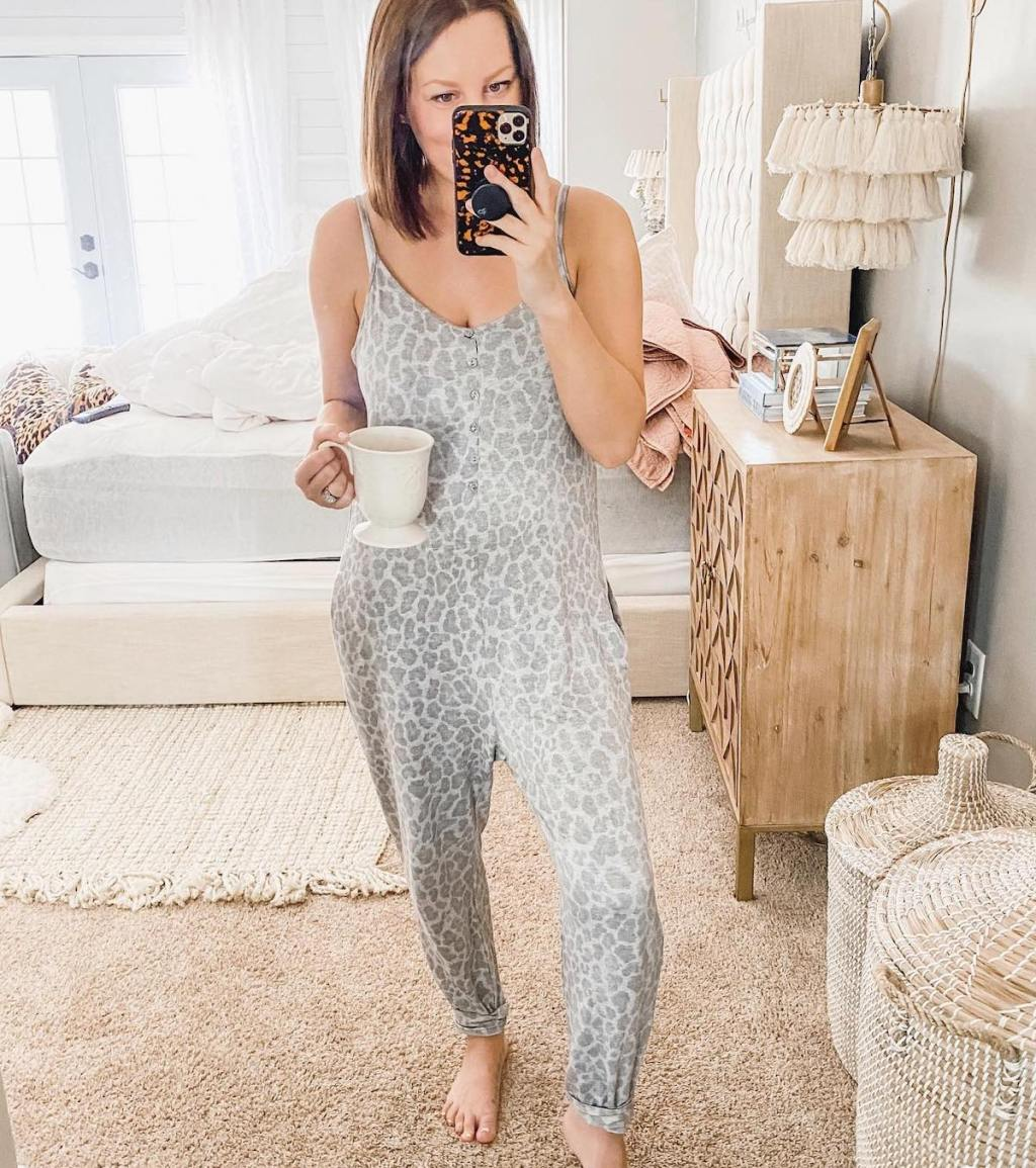 woman wearing gray and white leopard print jumpsuit standing in bedroom