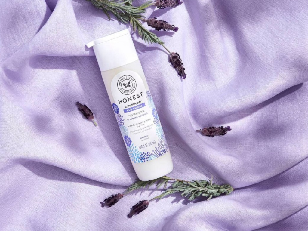 bottle of the honest company conditioner on a purple blanket with purple flowers