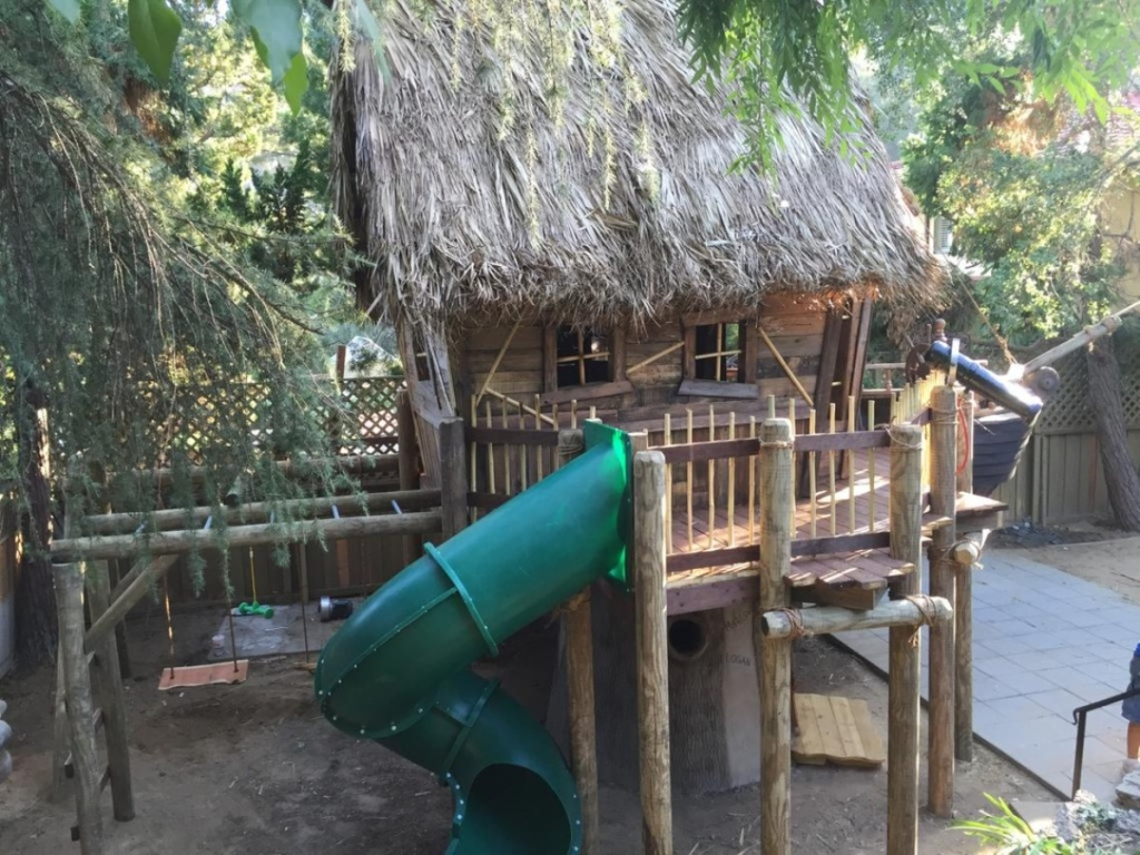 playhouse with tiki roof and green slide