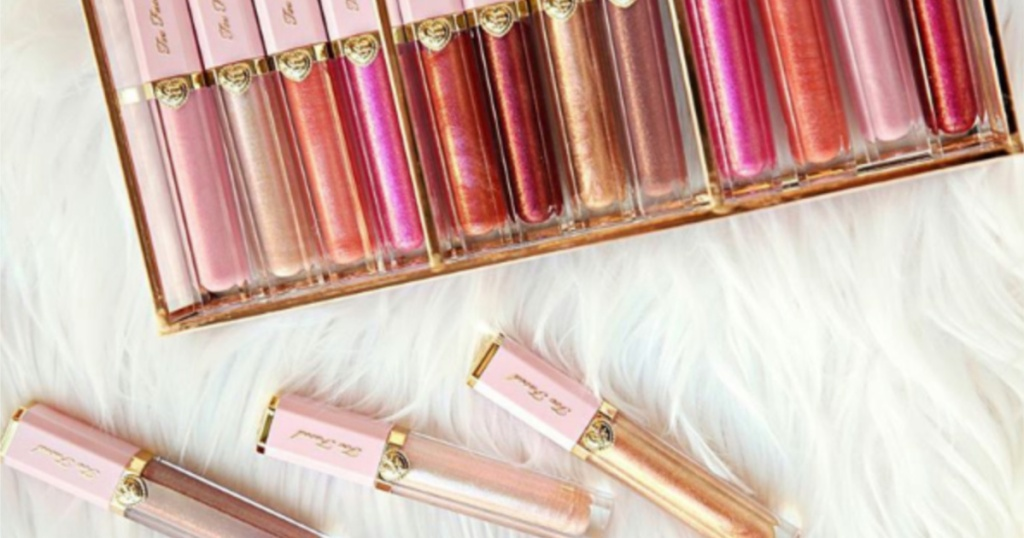 too faced lip glosses in box and on white furry surface