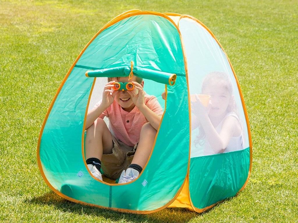 boy using binoculars in tent