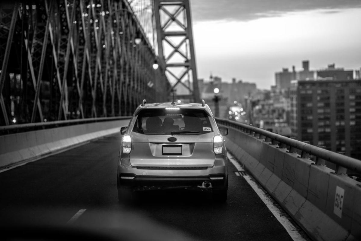 rear of Uber car driving over bridge