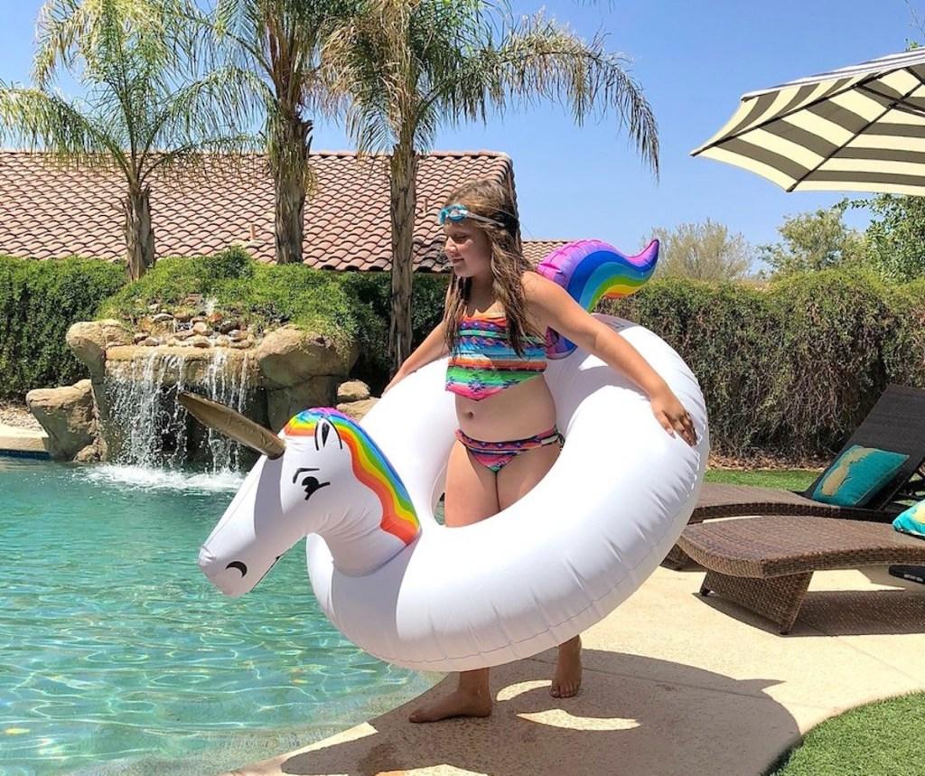 girl wearing unicorn pool float around waste