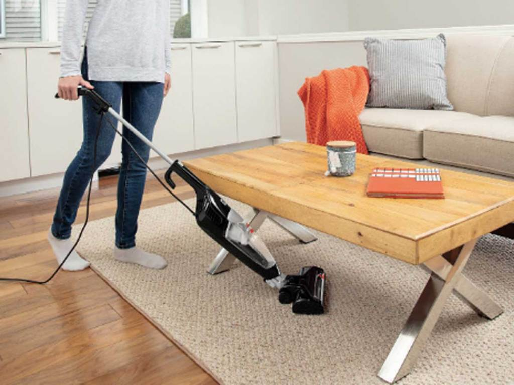 woman vacuuming under her coffee table in a living room