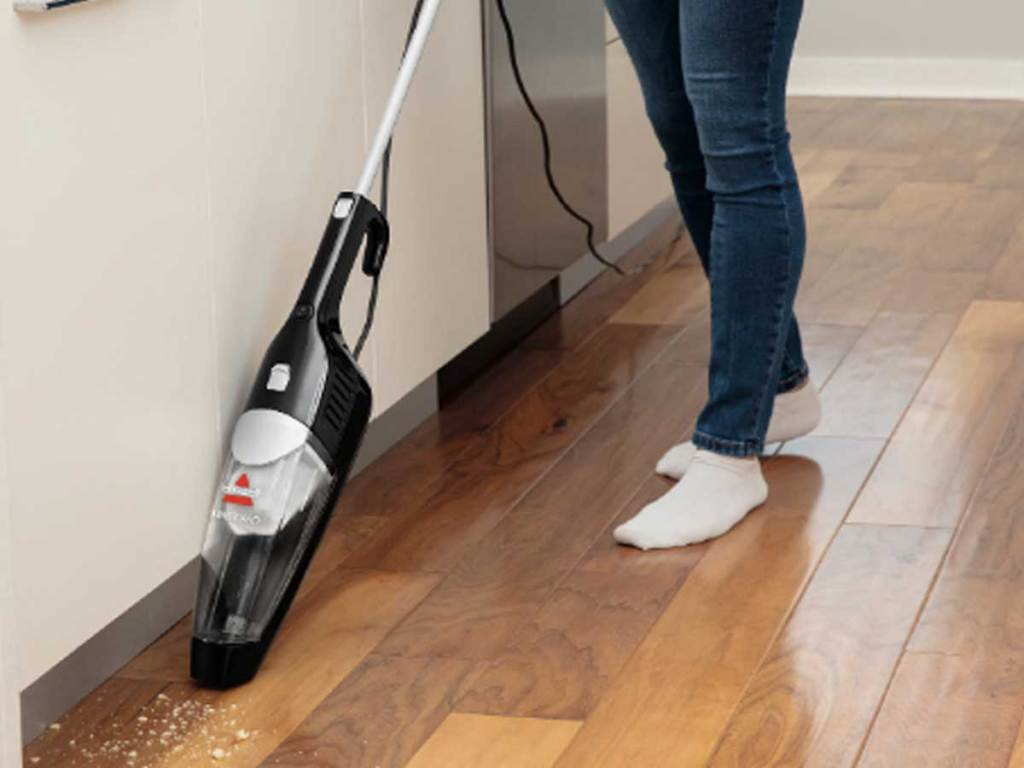 woman using stick vacuum in her kitchen