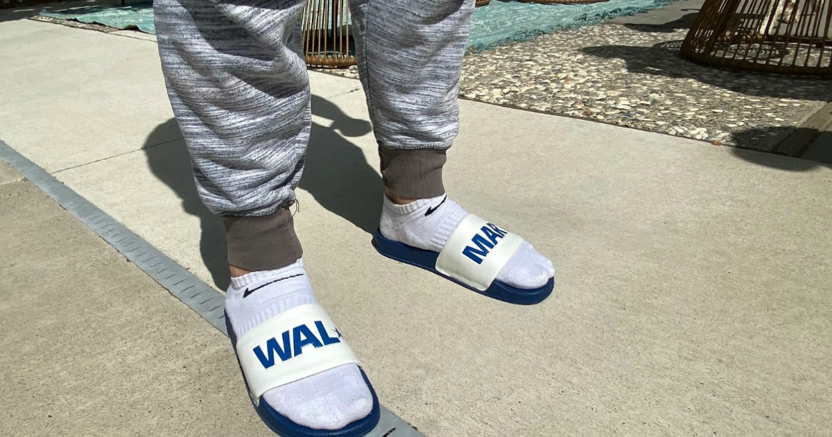 man wearing Walmart slides with Nike socks and sweats on