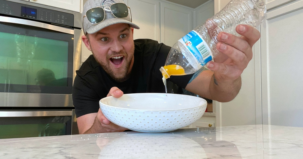 man looking at water bottle, bowl, and egg
