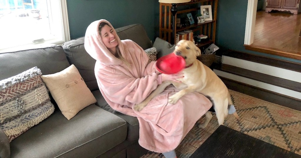 woman wearing large pink blanket playing with dog on couch