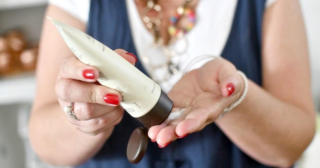 woman putting on ahava hand cream