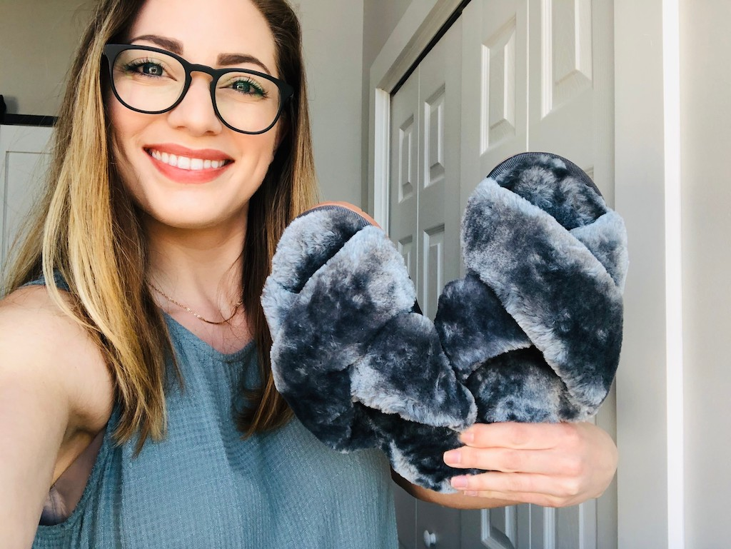 woman holding fuzzy grey slippers