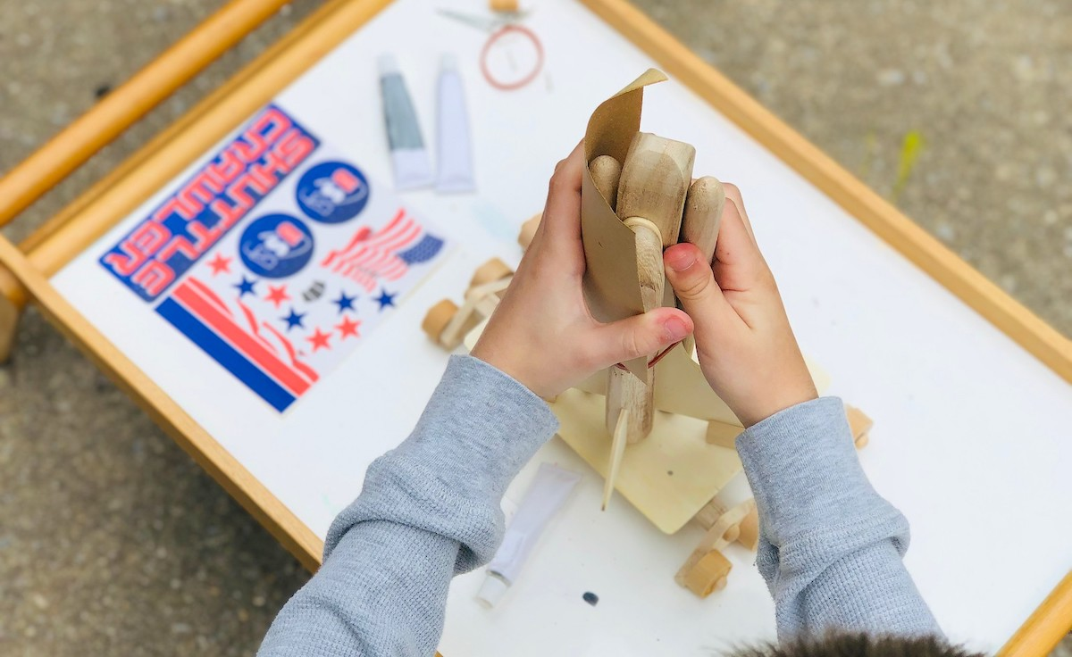 boys hands holding a wood rocket ship while sanding down sides