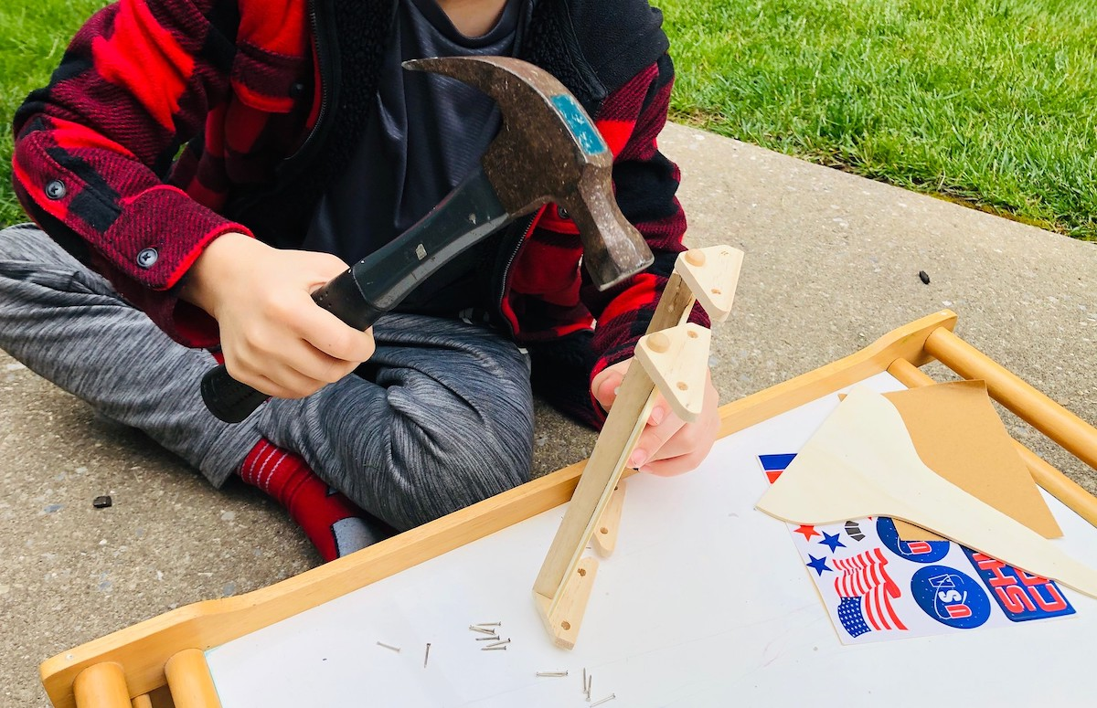 kid holding a hammer hitting nail into piece of wood