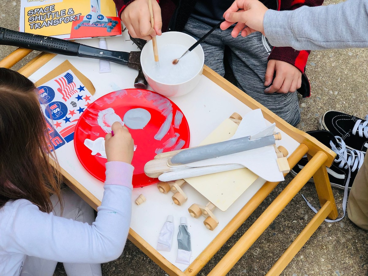 kids with paintbrushes painting wooden rocket ship on tray table