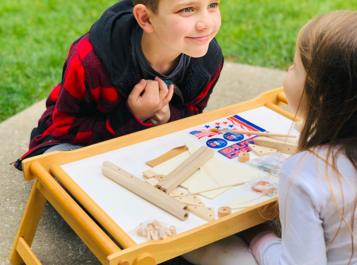 boy smiling with wood building materials on table
