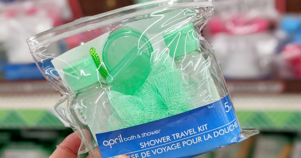 green travel shower kit with empty bottles pill organizer, and loofa, in a clear pouch