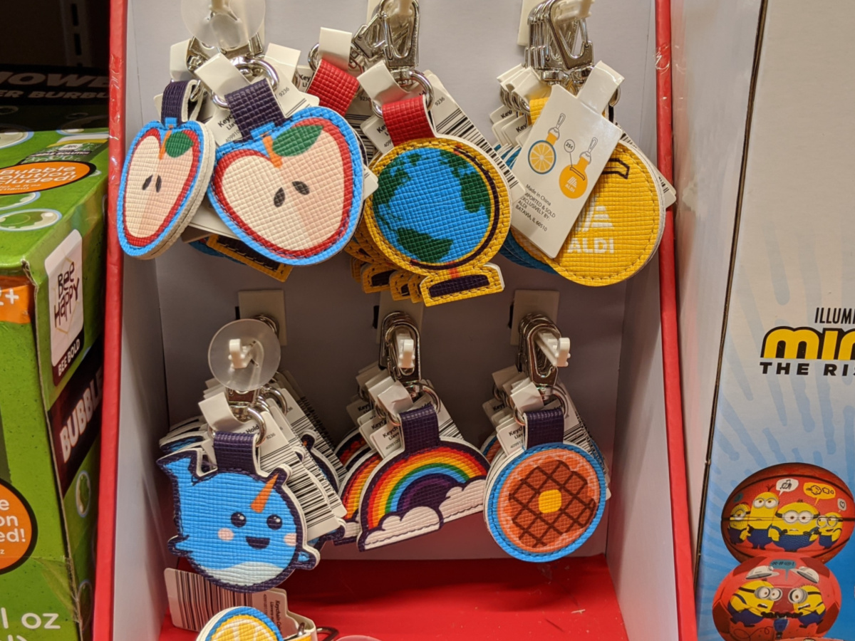 apple globe narwhal rainbow and waffle key chain coin holders hanging on display in sore